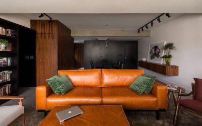 Apartamento cosmopolita mistura madeira, couro, concreto e tons escuros